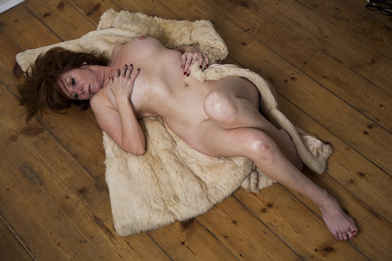 Portrait of a woman laying on fur coat