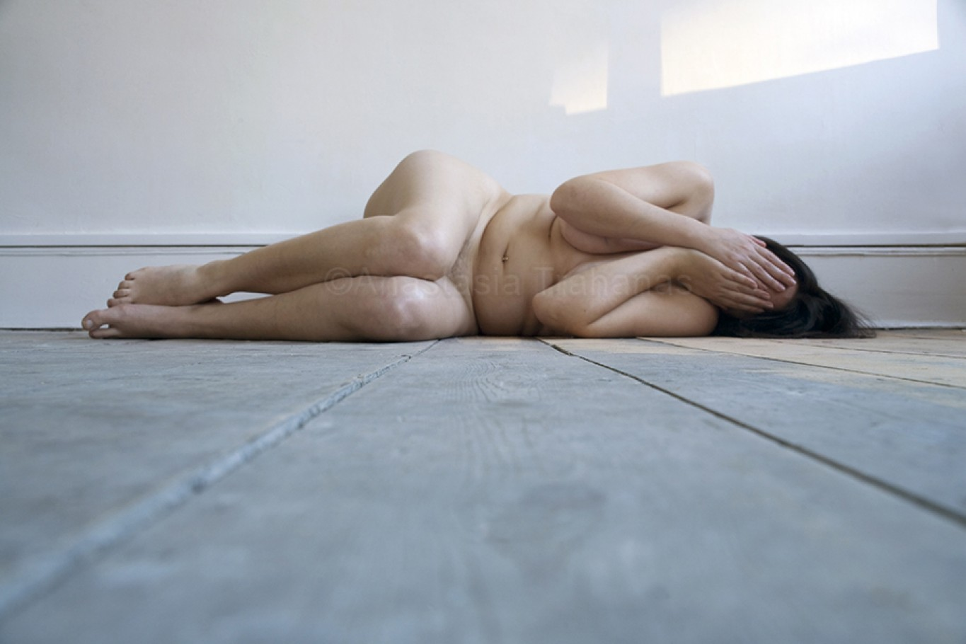 nude woman laying on floor