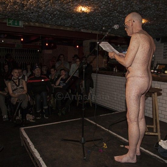 naked man reading poetry on stage