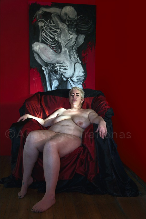 Nude woman seating on armchair