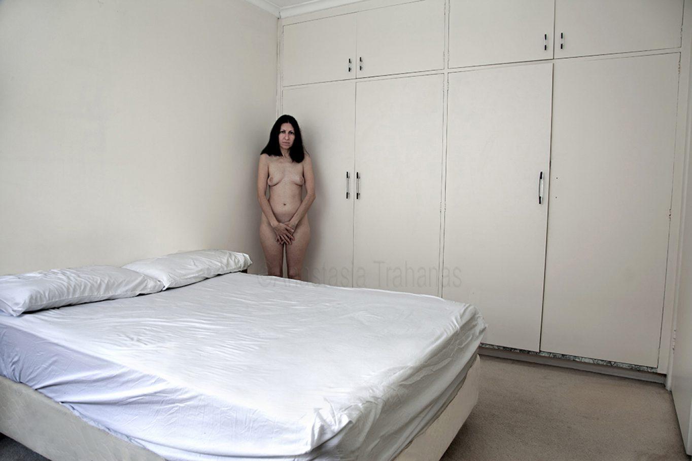Naked in corner of bedroom
