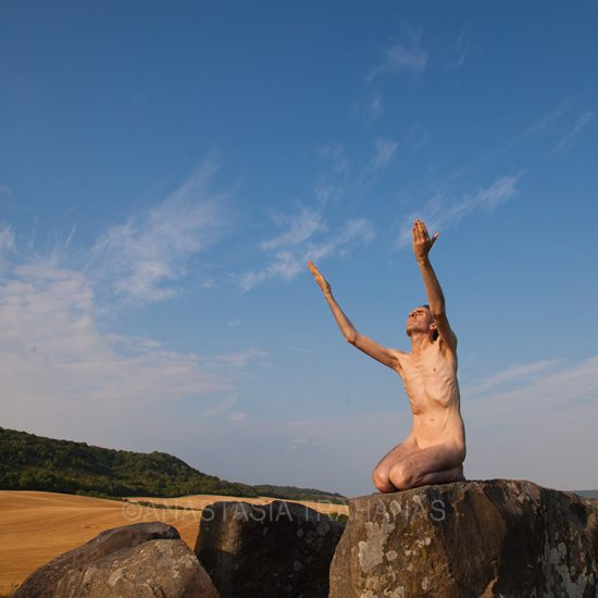 naked man on rock sun worshiping