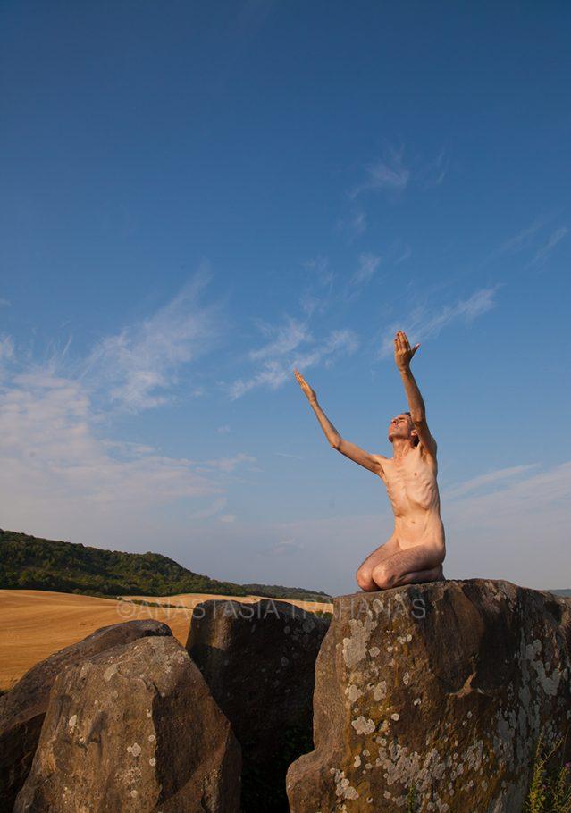 naked man on rock sun worshiping