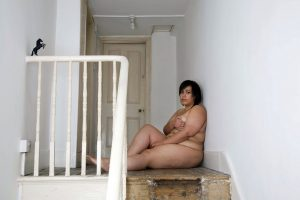 Naked woman seated on floor